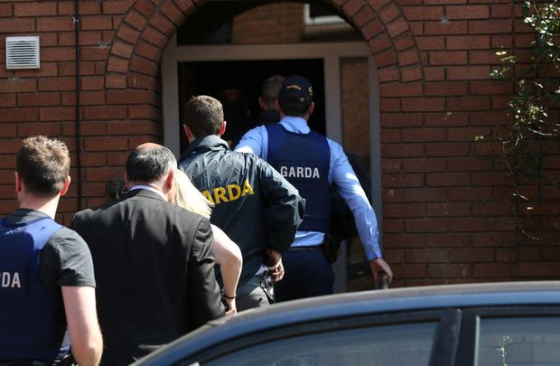 Above, gardaí raiding a home near the scene of the murder Picture: INM
