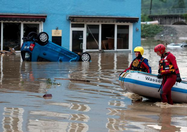 Rescue workers check homes in Simbach, Germany, for stranded householders after parts of France and Germany were flooded by torrential rains (AP)
