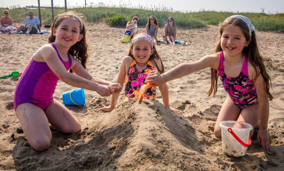 Sisters Sadhbh (5), Emma (10) and Aoife Keating Harte (7), Templeogue, enjoy the sunshine at Skerries beach Photo: Arthur Carron