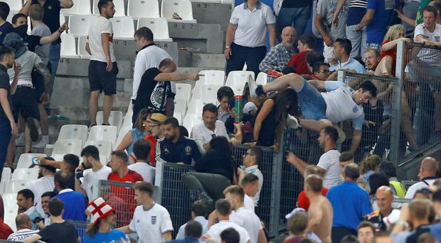 Crowd trouble: Fans scramble over fencing to escape hooligans as scuffles broke out after the England vs Russia game in Marseille Photo: Kirsty Wigglesworth