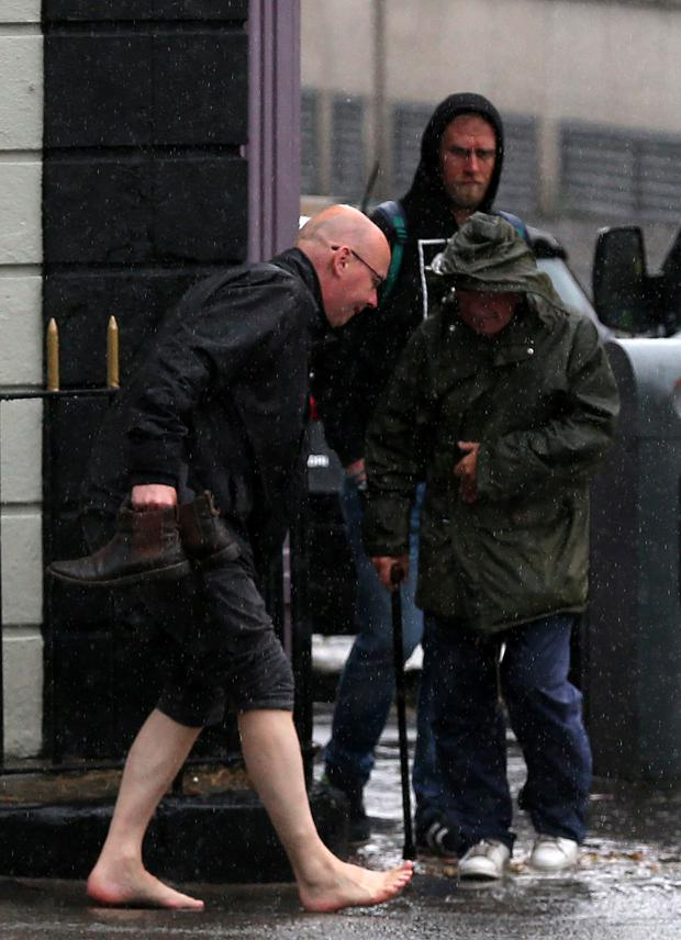 Members of the public get caught in a torrential downpour on Parkgate Street in Dublin. Photo: Laura Hutton/Collins Photo Agency