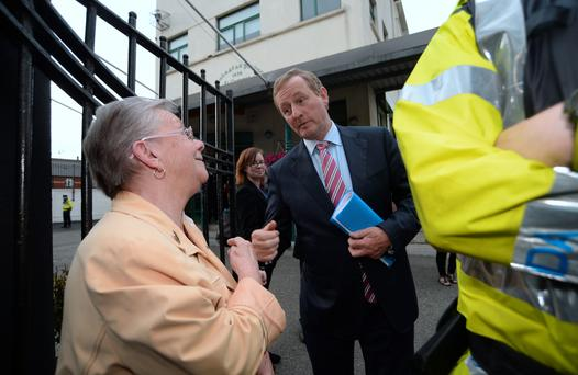 Taoiseach Enda Kenny greets local woman Kathleen Pickett as he arrives for a meeting at St Laurence O'Toole National School on Seville Place in Dublin. Photo: Caroline Quinn