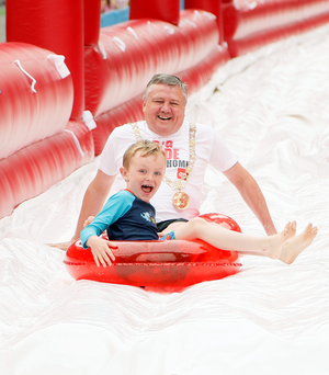 Dublin's Lord Mayor, Brendan Carr, with his son Jason (7) enjoying 98FM's Big Slide on Winetavern Street in Dublin this weekend