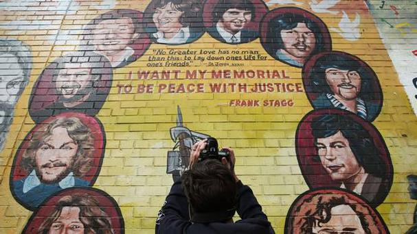A tourist takes a photo of a mural painted on the peace wall on Divis Street, Belfast. Photo: PA