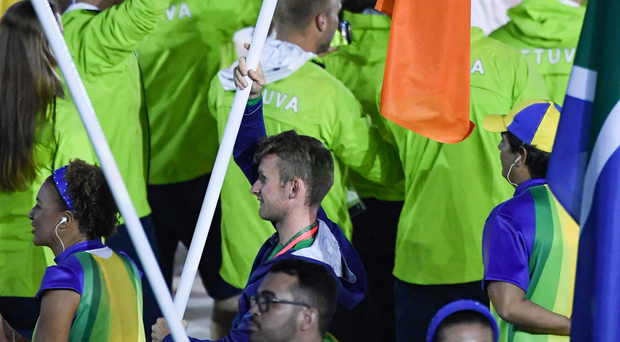 Gary O'Donovan carries the Irish flag during the closing ceremony of the 2016 Olympic Games at the Maracana Stadium last night Photo: Ramsey Cardy