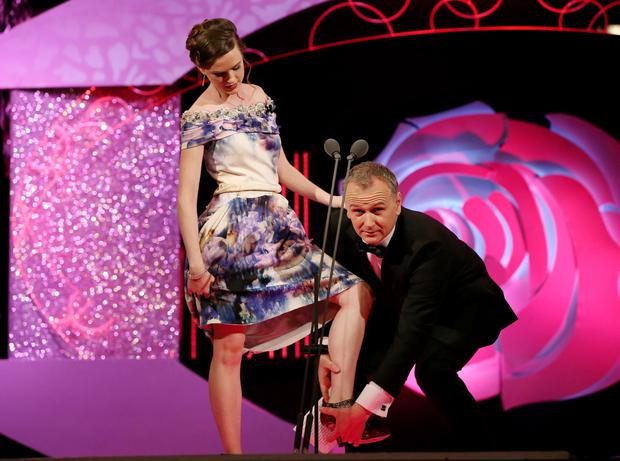 Dáithi Ó Se helps Ohio Rose Kathleen Rose O Donnell to take off her shoes before her hoop dance