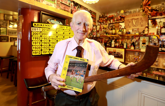 Seamus Delaney with a hurley which was made in 1890 and the first colour programme from the 1967 All-Ireland hurling final Photo: Frank McGrath