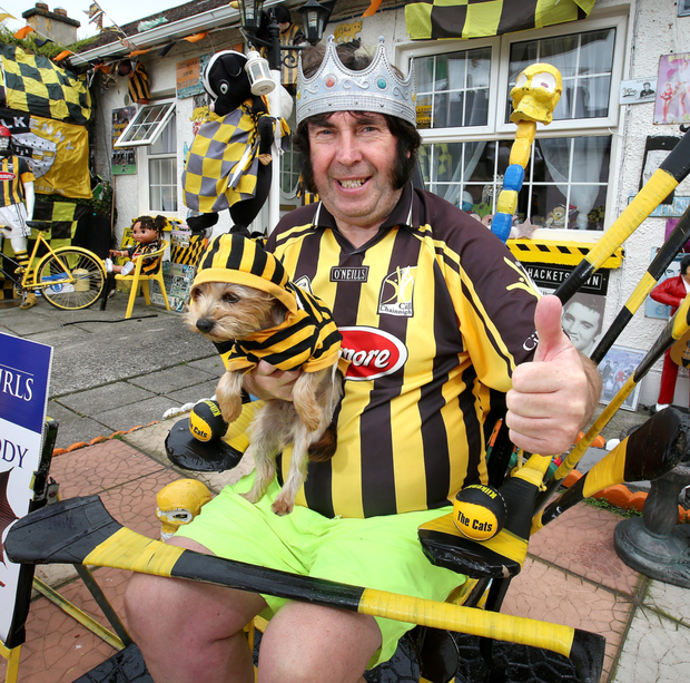 Kilkenny fan Myles 'Elvis' Kavanagh with his dog Priscilla at his shrine to Kilkenny hurling in his front garden at Thomas Square in Kilkenny Photo: Frank McGrath