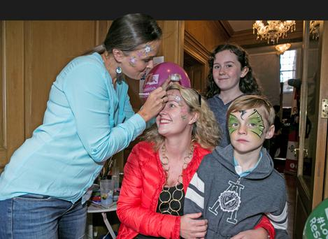 Caoilfhionn Groarke, from Killiney, with her son Euan (8) and daughter Romilly (11), getting their faces painted in Boston College Picture: Kyran O'Brien