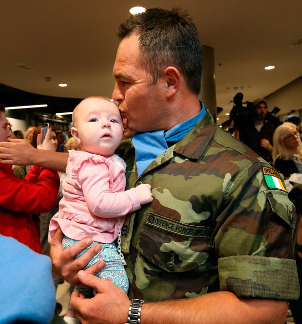 Sgt Ciaran Smithers pictured with his daughter Emily [6 mths], after the 52 Infantry Batt returned to Dublin Airport after a six month deployment to the Golan Heights. Picture Credit : Frank Mc Grath