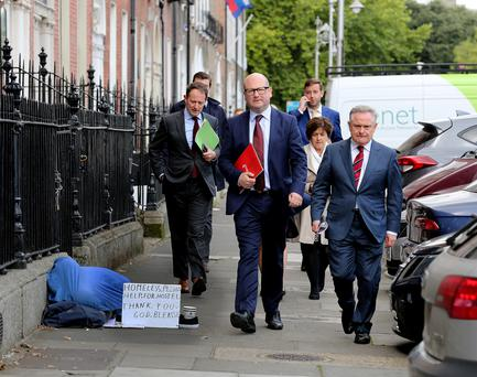 Labour Party leader Brendan Howlin (right) with TD Sean Sherlock (left) and Senator Ged Nash pass a homeless person on their way to the launch of the party's alternative Budget 2017 in Dublin's Merrion Square. Photo: Tom Burke