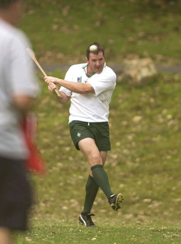 Anthony Foley practises his hurling skills after training at the 2003 World Cup. Photo: Brendan Moran