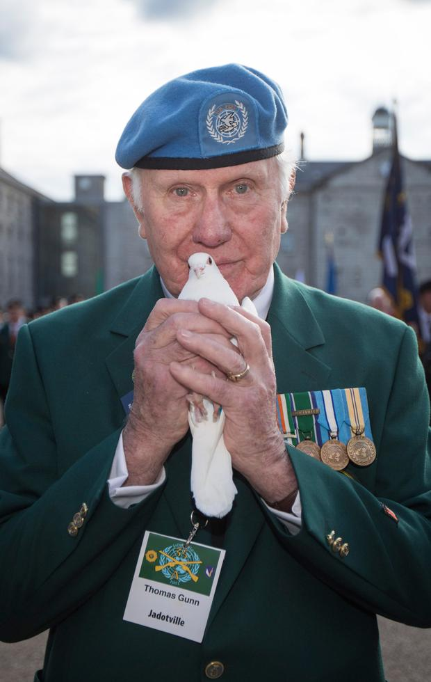 Poignant symbol: Thomas Gunn (78), one of the survivors of the Siege of Jadotville in the Congo, with one of the 21 doves that were released into the sky yesterday in tribute to the Irish peacekeepers Photo: Fergal Phillips