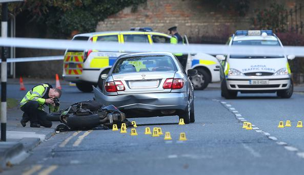 A forensic officer takes photos at the scene in Dún Laoghaire where a motorcyclist was killed. Photo: Damien Eagers