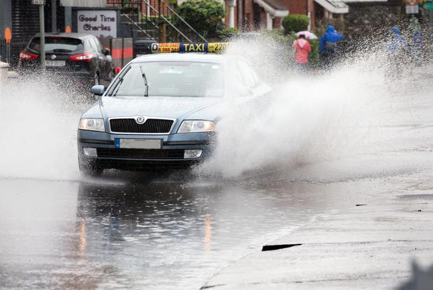 A taxi drives through floods in Phibsboro, Dublin, yesterday. Photo: Tony Gavin