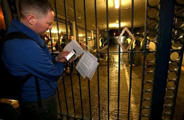 Direct action: Noel Scurry, of the Home Sweet Home pressure group, examines the High Court notice to vacate Apollo House, posted last week on the building's gates. Photo: Gerry Mooney
