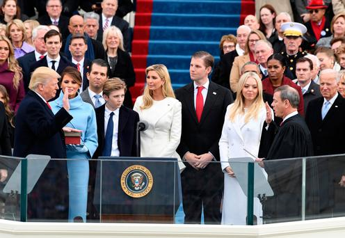Donald Trump, left, takes the oath of office with Supreme Court Chief Justice John Roberts in front of his family. Photo: Bloomberg