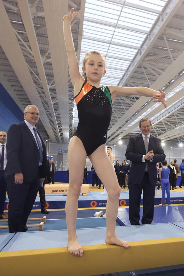 Taoiseach Enda Kenny watches Emma Morgan (9) perform at the opening of the new Sports Ireland National Indoor Arena in west Dublin. The €40m facility at the National Sports Campus in Abbotstown will cater for at least 20 sports and features a retractable 200m banked running track, 60m and 110m sprint tracks, pole-vault areas and seating that can be extended to nearly 2,000 spectators. Photo: Damien Eagers