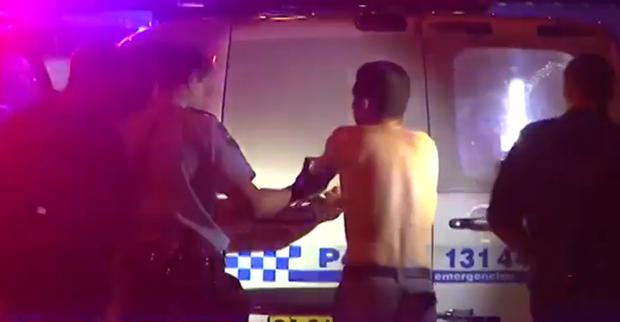 A man is held by police at the scene of the stabbing in Sydney