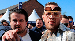 Unique style: Conor McGregor flashes his tattooed torso after arriving at Aintree Racecourse yesterday for Grand National Day. Photo: Peter Byrne/PA