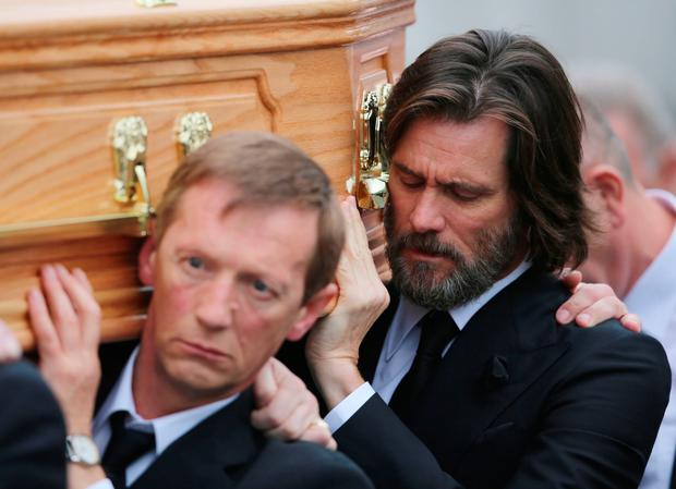Actor Jim Carrey carries the coffin of his former partner, Cathriona White