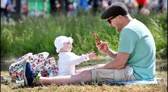 Nathan Jamieson and his daughter Lucy (7 months) from Tallaght, Dublin, enjoying the sunshine. Photo: Steve Humphreys