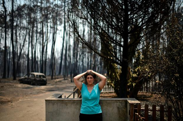 Anabela Silva stands in front of her house with her burnt car in the background Photo: Getty