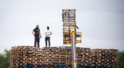 Masked men continue to build a bonfire at Inverary Playing Fields in Belfast. Photo: Liam McBurney/PA Wire