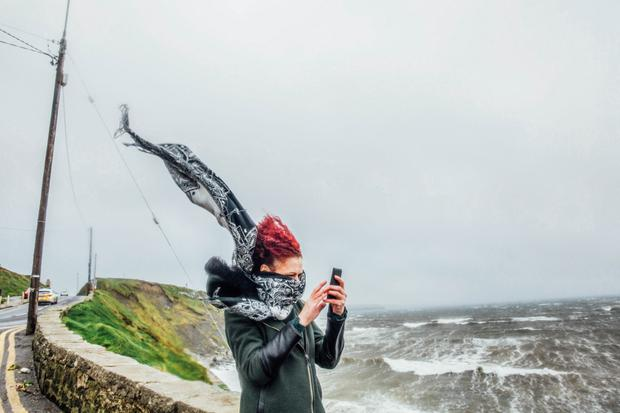 Gina Casey, from Ennistymon, struggles with the high wind on the Lahinch coastline of Co Clare. Photo: Brian Arthur