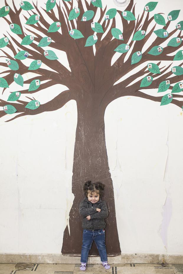 Three-year-old Nour, who was found alone and injured on the streets of Aleppo, stands in front of a tree decorated with the photos of other children who have been brought to a care facility for separated children. Photo: Mark Condren