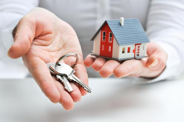 Real estate agent with house model and keys Photo: Deposit