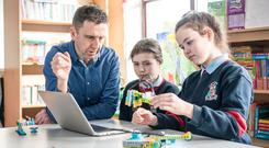 Attymass sixth class pupils Éadaoin O'Malley (11) and Jessica Feeney (12) work with Lego robots under the guidance of principal Sean Gallagher Photo : Keith Heneghan / Phocus