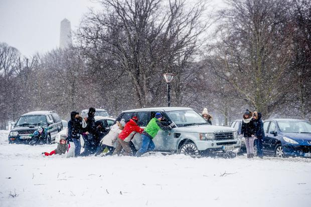 Passers-by help push a 4x4 out of the snow on Chesterfield Avenue, Phoenix Park, Dublin. Photo: Conor McCabe