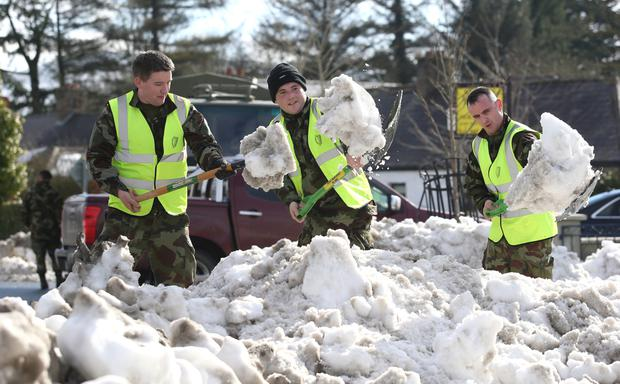 Private Mark Fitzpatrick, Private Kevin McKerr and Cpl John Rooney, from the 27th battalion in Dundalk, clearing snow from Blessington village in Wicklow. Photo: Damien Eagers