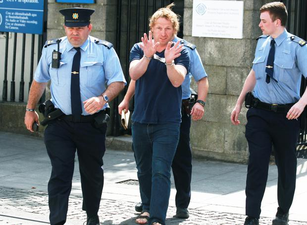 John Kinsella as he is escorted to the holding cells in the nearby Bridewell garda station during the lunch break period Photo: CourtPix