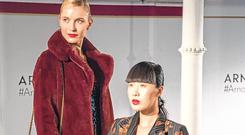 Teo wears a burgundy faux fur jacket (€250), pleated dress (€260), both Karen Millen, a Coach bag (€595) and boots by Jonak (€189). Yomiko wears a DmN coat (€760), a Marella jumpsuit (€240) and shoes by Miss KG (€80).