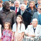 Main: President Michael D Higgins with family members of Big Tom, including his sister Margaret Kavanagh (front right) and his son Thomas (in between the statue and the President) after the unveiling in Castleblayney yesterday. Photo: Brian Lawless