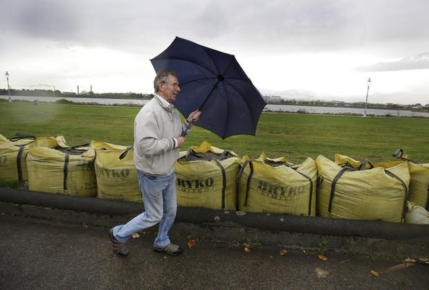 Pat Duane, from Glasnevin, walks in driving rain past sandbags in Clontarf, Photo: Damien Eagers