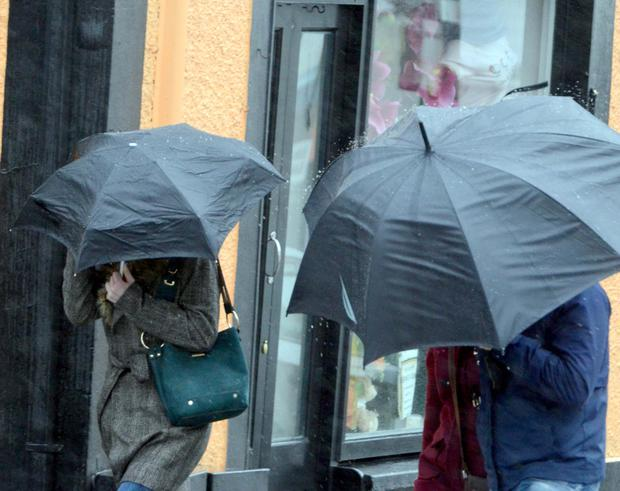Stormy: Locals struggle with brollies in Westport, Co Mayo, as the wet, windy weather moves in. Photo: Paul Mealey
