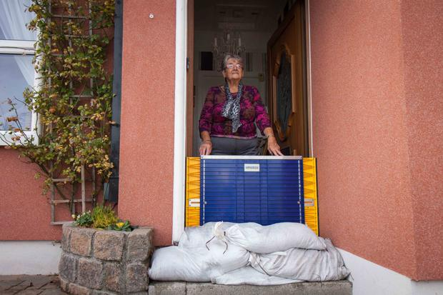 Nancy Long stands at the door of her house in the Claddagh Quay in Galway with sandbags and a plastic flood gate for protection against possible flooding from Storm Callum. Photo: Andy Newman