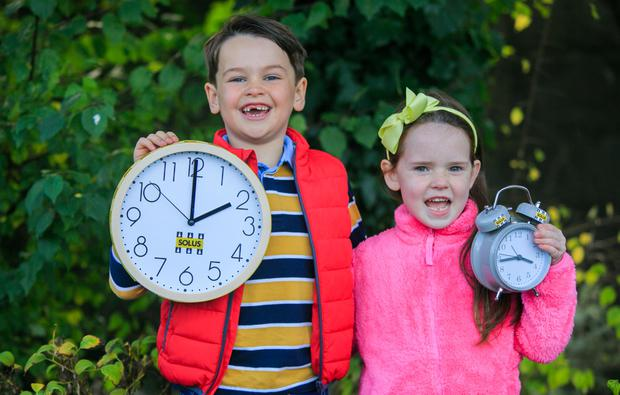 Set your alarm: Hugo Stone (6), from Ratoath, Co Meath, and Aimee Driver (6), from Co Wicklow, remind everyone to turn their clocks back. Photo: Gareth Chaney