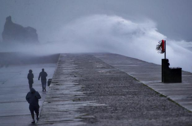 Wild: Walkers on the harbour in Howth, Co Dublin. Photos: Colin Keegan/Collins