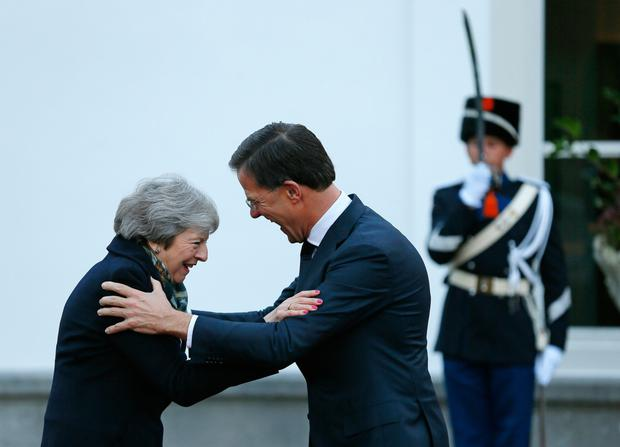 Get a grip: Theresa May is greeted by Dutch Prime Minister Mark Rutte in the Netherlands. Picture: AP