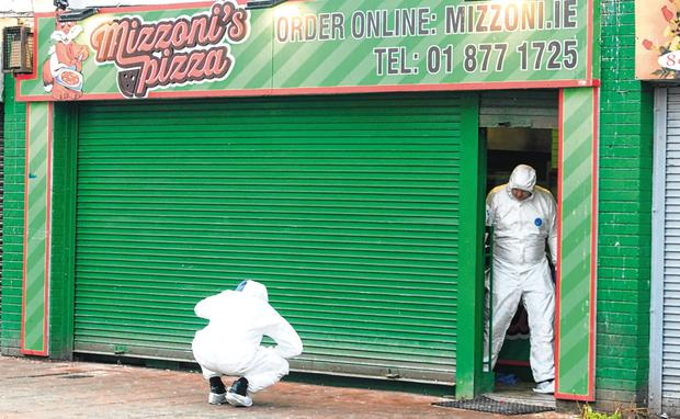 Murder bid: Forensics gardaí at the scene of the shooting at a takeaway in Edenmore, Dublin. Photo: Gareth Chaney/Collins