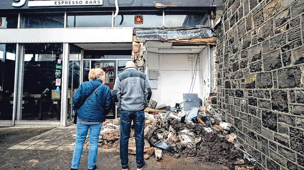 Passers by look at the scene in Market Square in Bushmills, Co Antrim, after a digger was used in an early-morning attack to rip a ATM from the wall of a shop. PA
