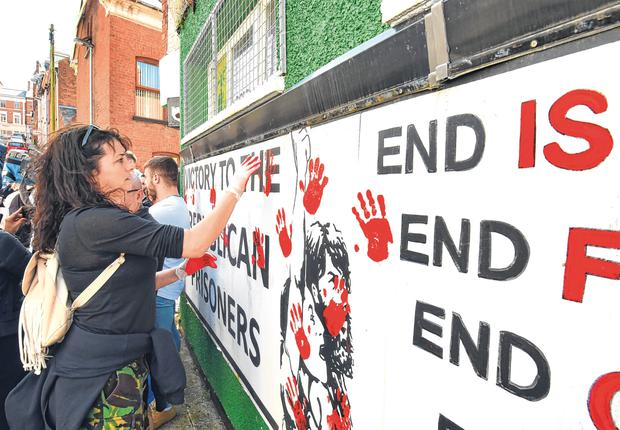 Hand delivered: Friends of Lyra McKee paint blood-red handprints on the Derry office of dissident republicans. Photo: Trevor McBride