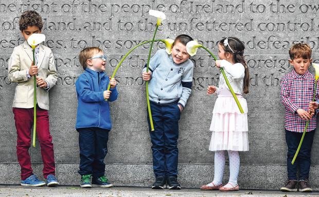 1916 Rising memorial: Eoin Carroll (9), Charlie McAllister (3), Cillian Devlin (6), Torah Devlin (5) and Conor McMorland (6) with lilies in front of the commemoration wall at Arbour Hill cemetery. Photo: Gerry Mooney