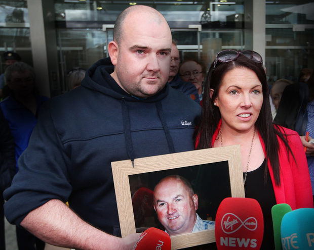 Bobby Ryan's children Robert and Michelle hold a photo of their murdered father outside court last week. Picture: Steve Humphreys