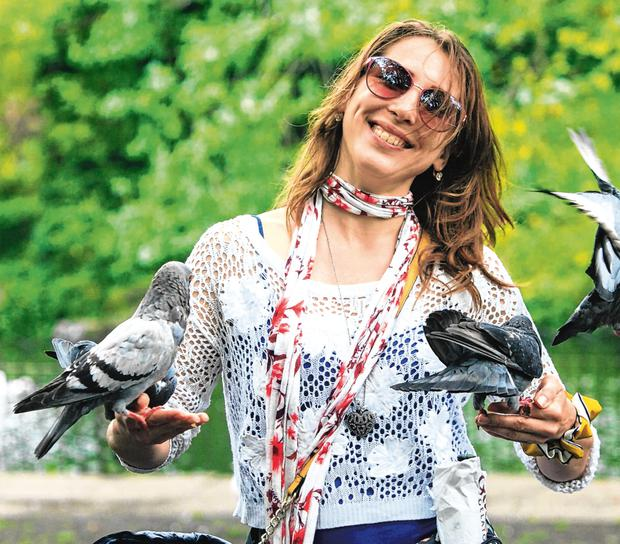 Feathered friends: Davis Leleikaite, from Ontario, Canada, feeding pigeons in St Stephen's Green in Dublin. Photo: Gareth Chaney/Collins