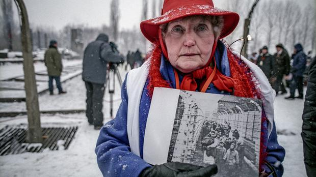 Survivor: Eva Mozes Kor on a return visit to Auschwitz, with a photo of herself and her twin